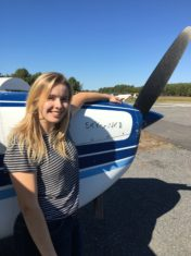 Cassie Standing resting her arm on a Plane propeller
