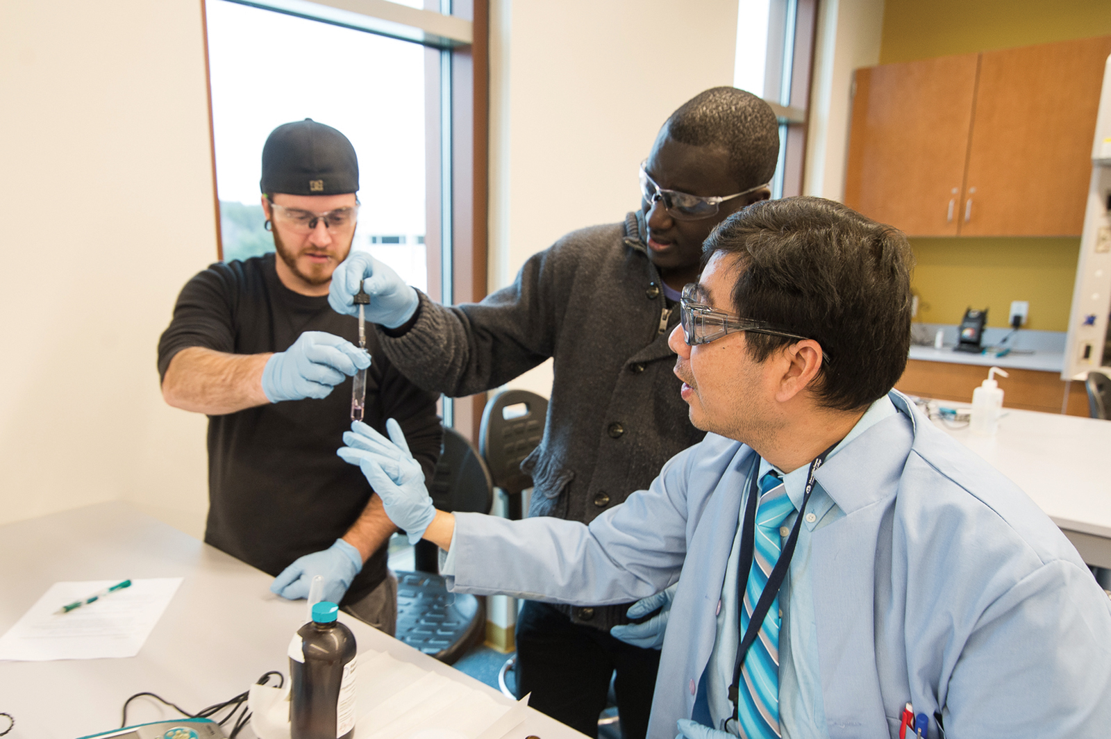 A professor instructs two students in a college science lab.