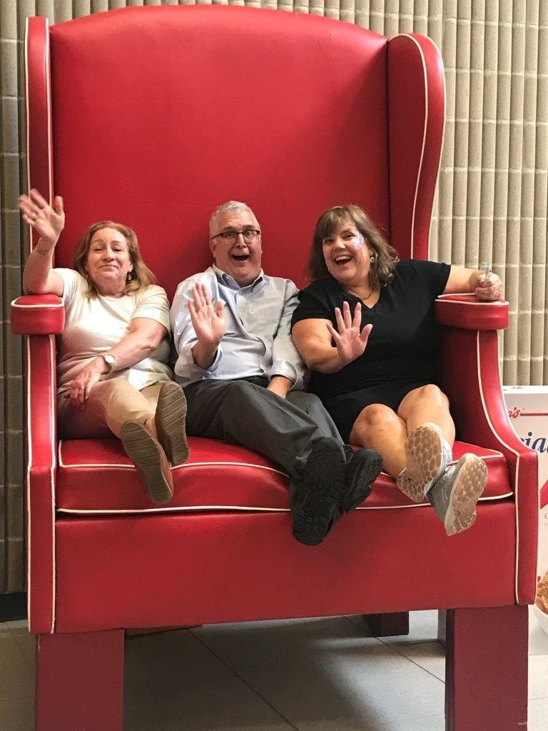 Three professors making silly faces while sitting in a giant red chair.
