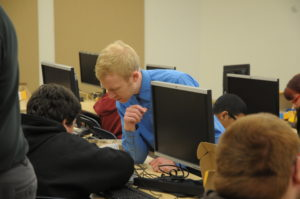 People work in front of computers as one person leans over helping one individual.