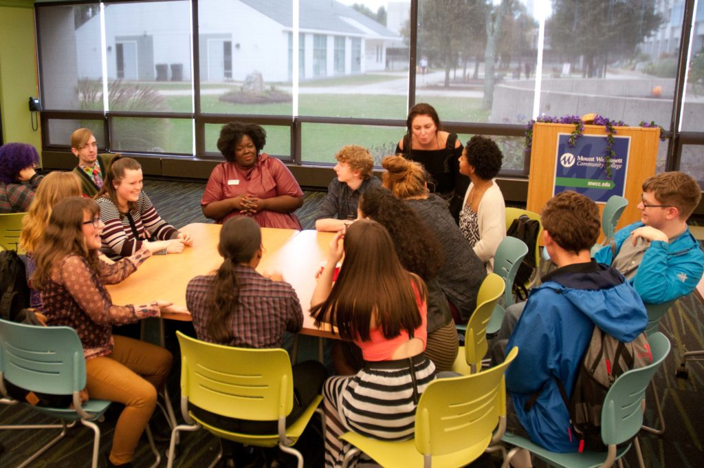 A group of students sits around a teacher as they have a discussion.