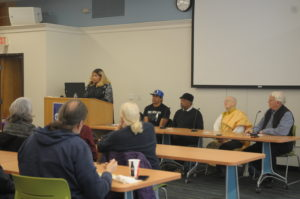 Four people sit at a table in the front of a room giving a presentation. To the left is the moderator at a podium.