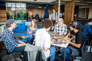 Photo of students sitting at a table in the Bemis Student Center playing a board game