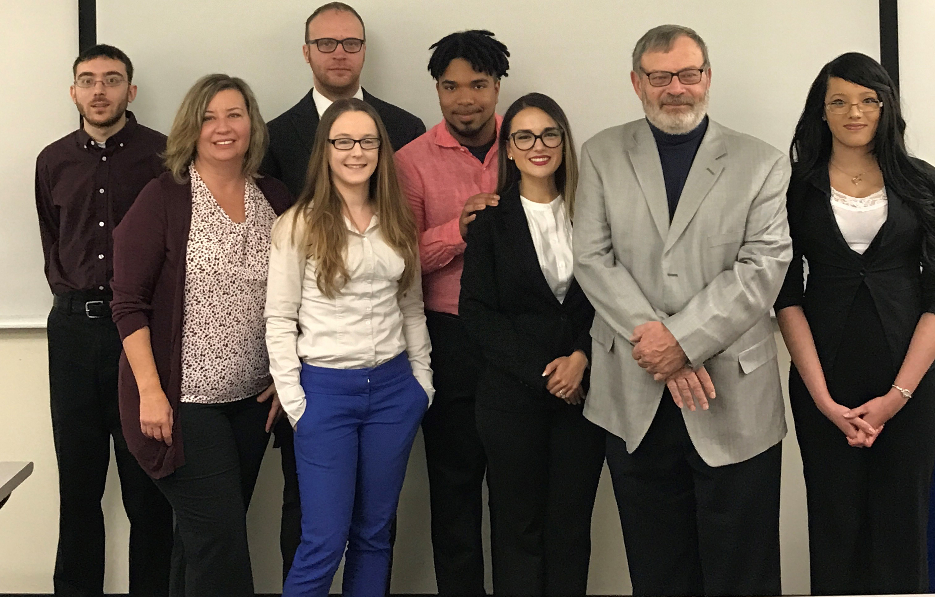 A photo of students in MWCC's 2018 Strategic Management Capstone class. Professor John Reilly and client Diane St. Jean are also depicted.