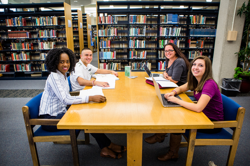 Photos of students sitting at a table in the library