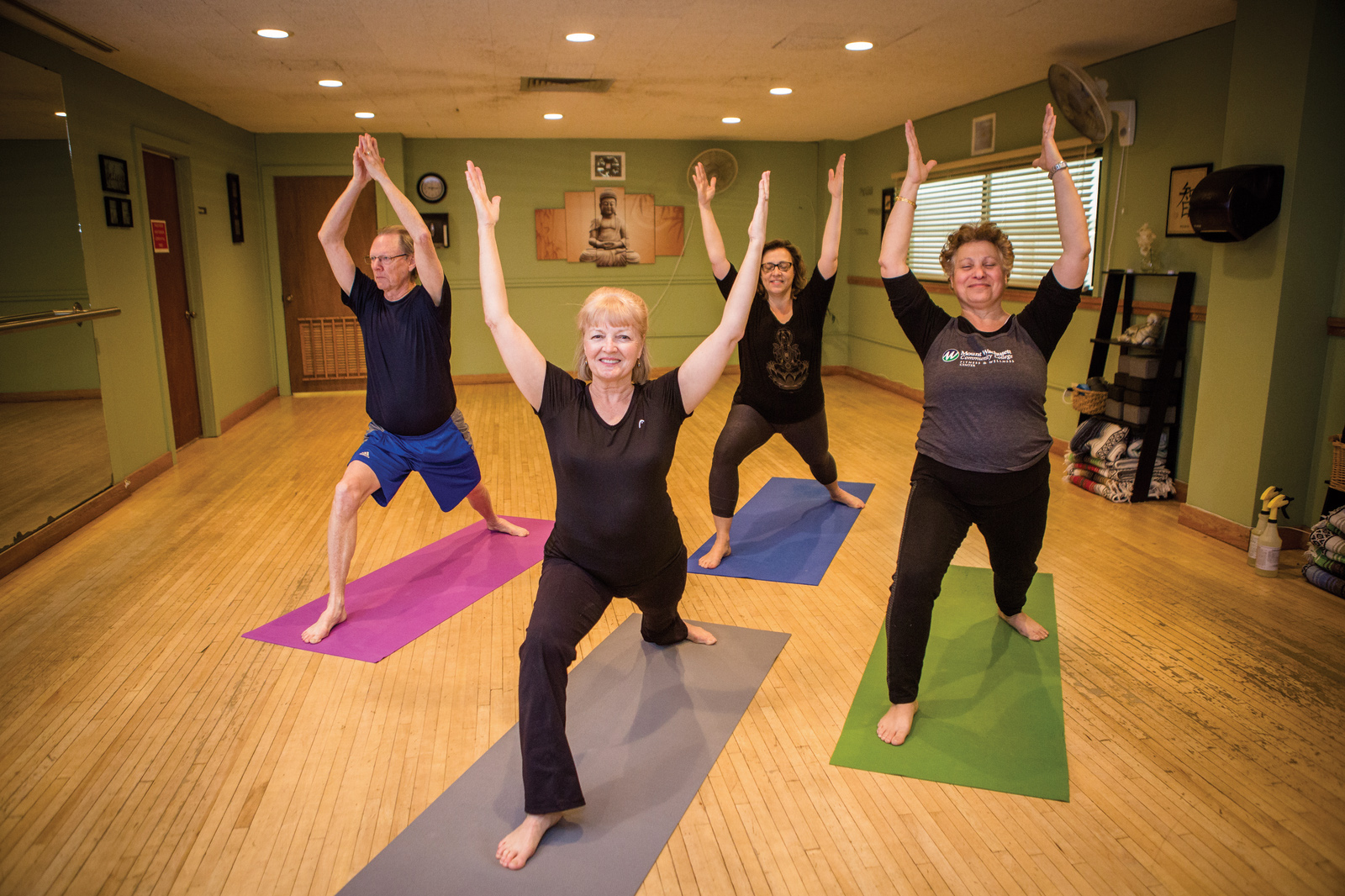 Four people do a yoga pose with their hands in the air.