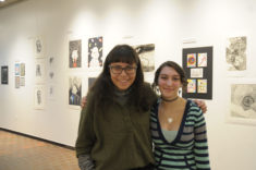 Two students stand next to each other in front of a white walled gallery space with artwork hanging on the walls.