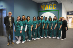 12 people stand in a line. The 10 students in the middle are dressed in nurses outfits.