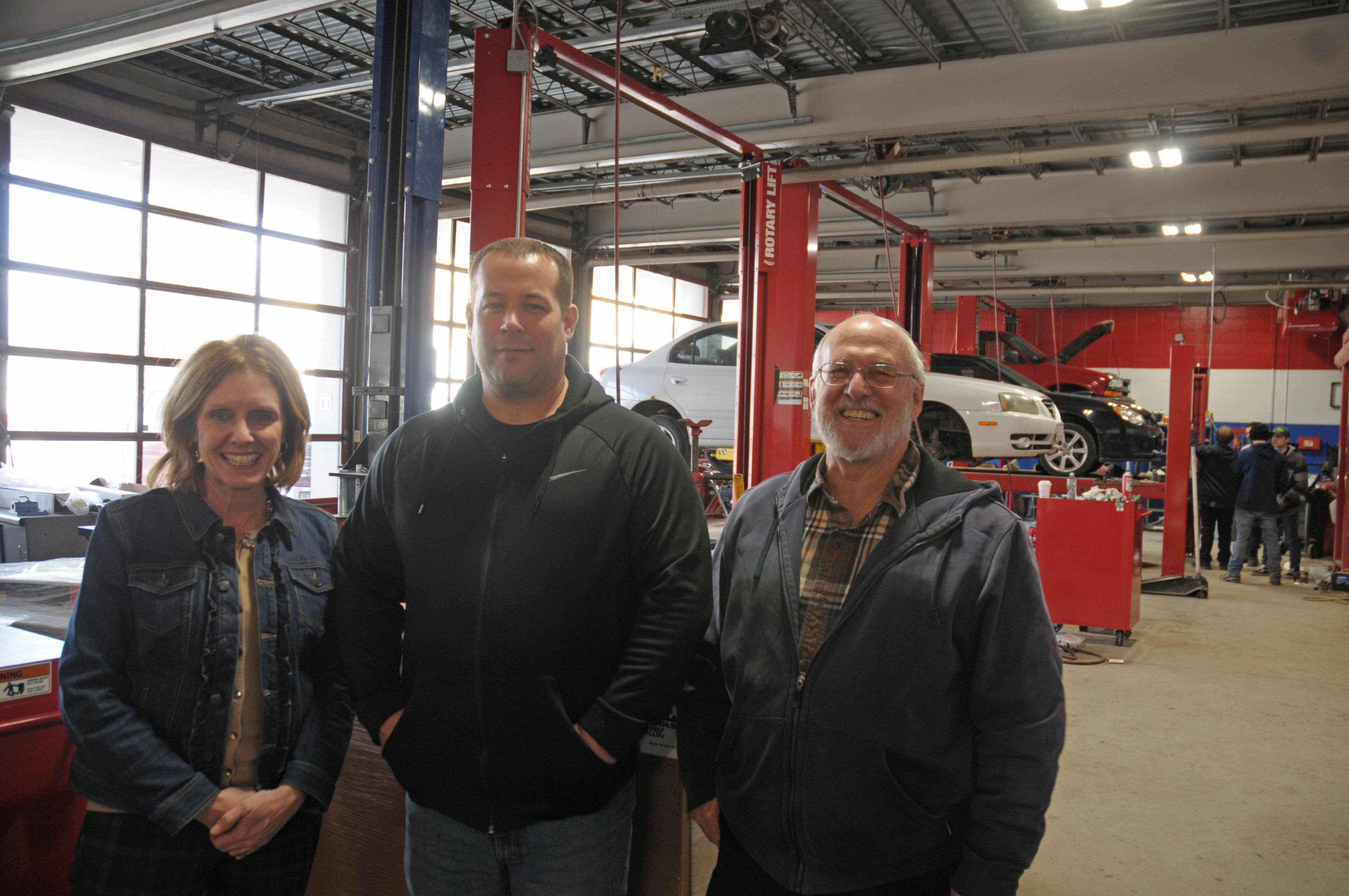 Three people stand in a row in an automotive repair area.