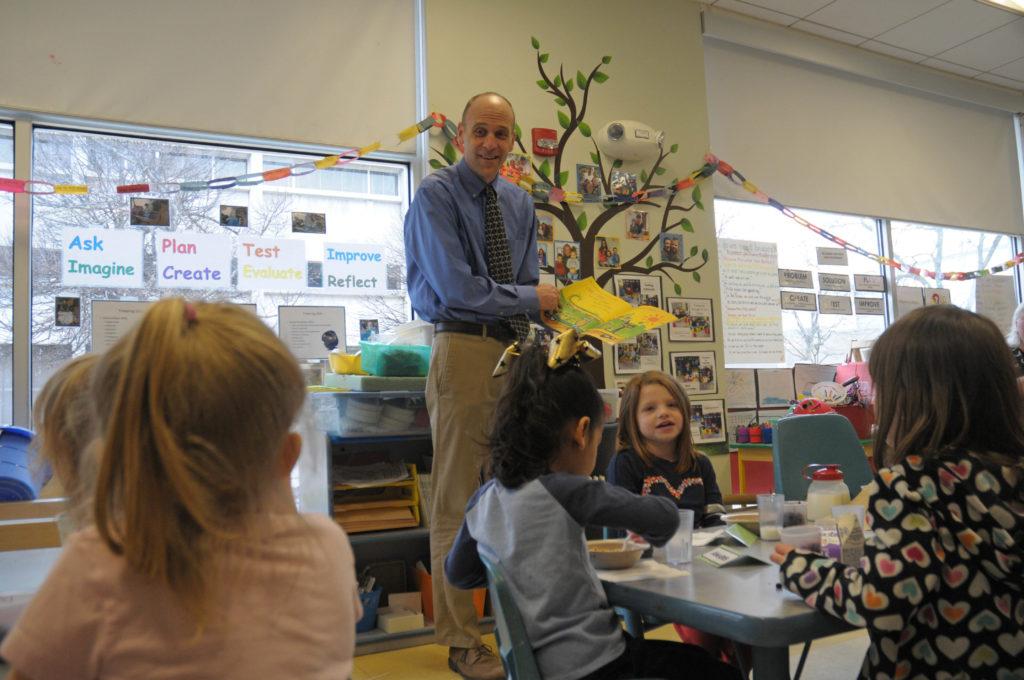 A man reads to children.