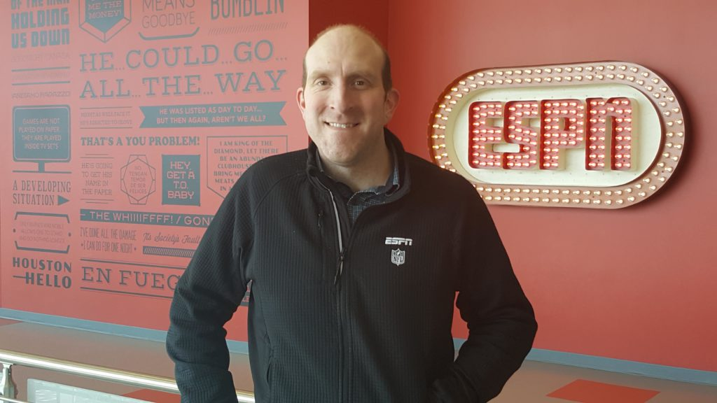 A man stands in front of an ESPN sign.