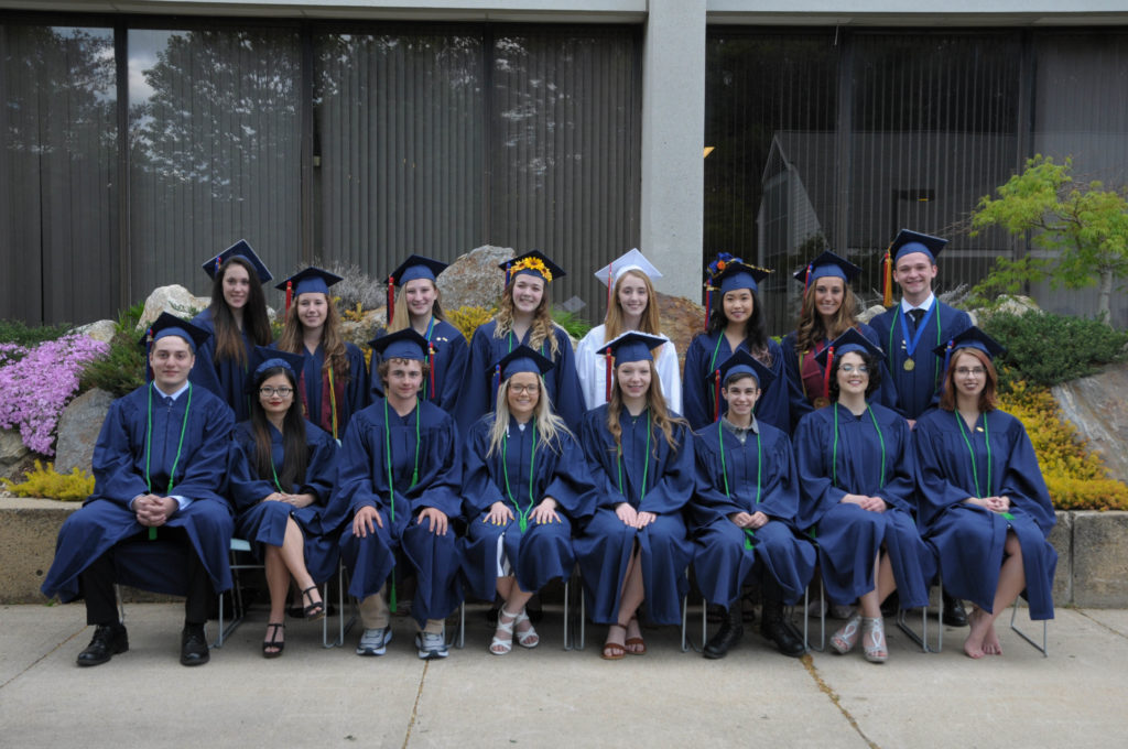 A group of students stands in graduation outfits.