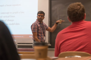 A professor stands in front of a blackboard teaching students.