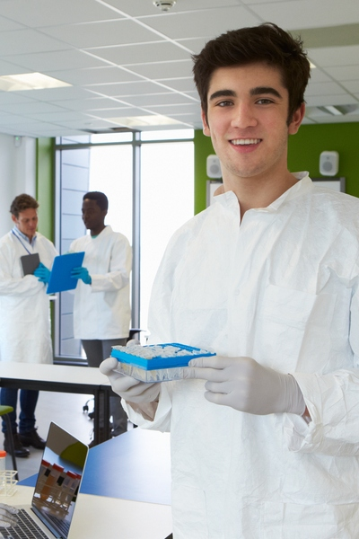 male student in white lab coat with vials