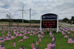 The grass is covered with American flags and a digital sign in the background gives information about the veteran's fair.