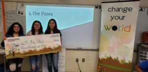 3 girls stand to the side holding a giant check