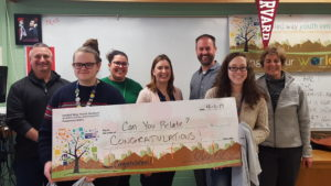 2 teens and 5 adults stand behind a giant check