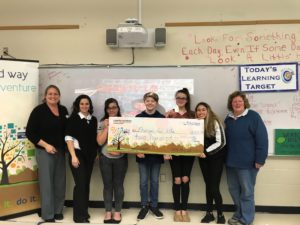 4 teens and 3 adults hold a giant check