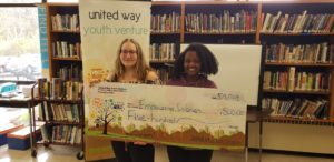 2 teens stand behind a giant check