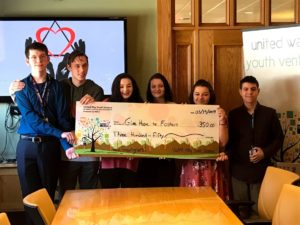 6 teens stand holding a giant check