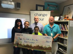 2 kids and 3 adults stand behind a giant check