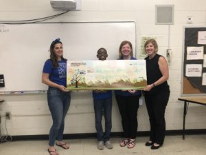 1 teen and 3 adults stand behind a giant check