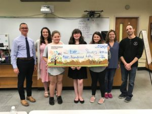 3 teens and 4 adults stand behind a giant check