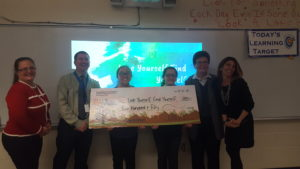 2 kids and 4 adults stand in front of a slideshow while holding a giant check