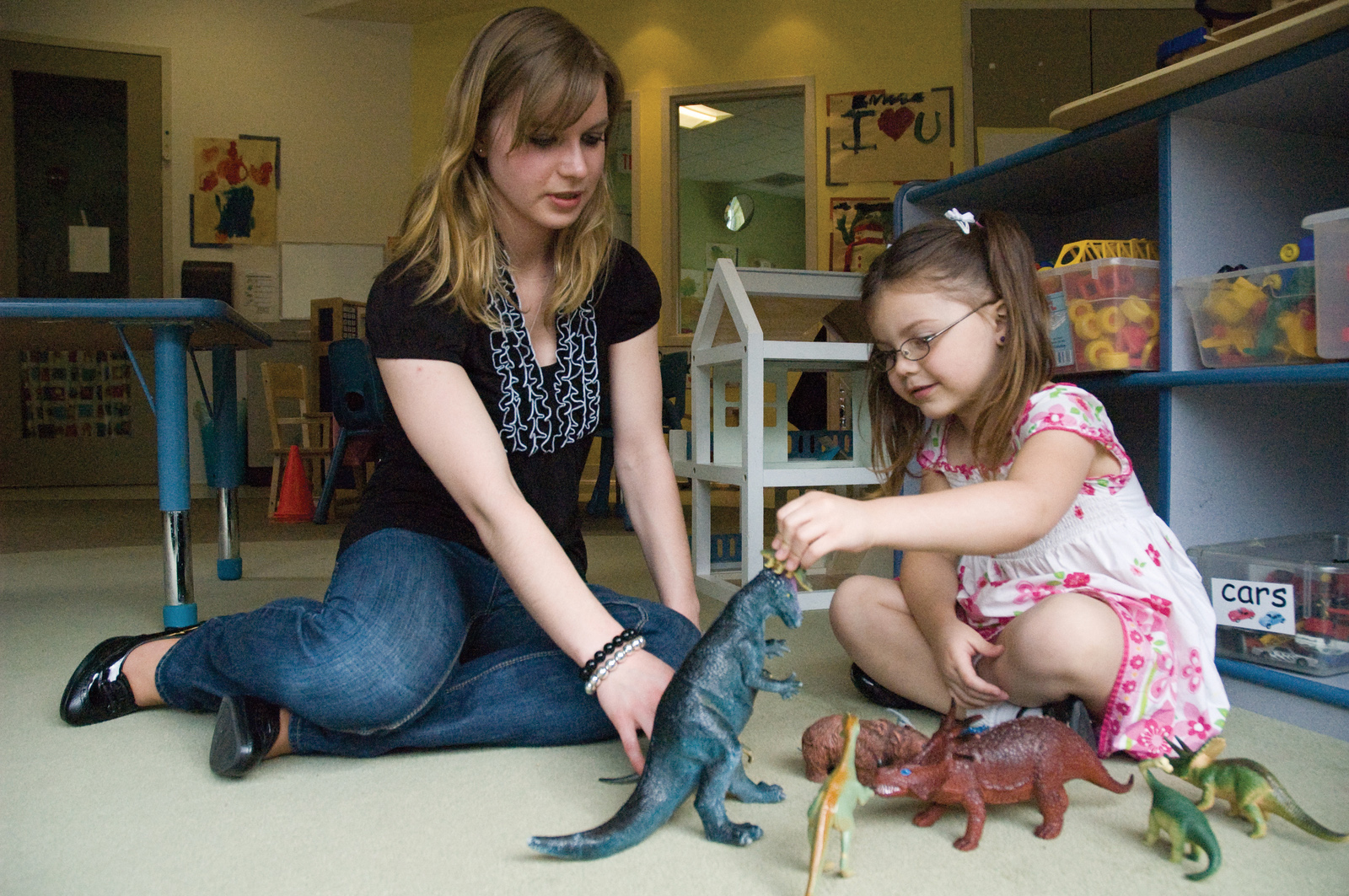 A woman interacts with a child who is playing with toy dinosaurs.