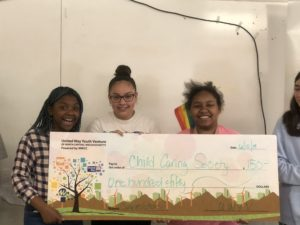 3 kids stand behind a giant check