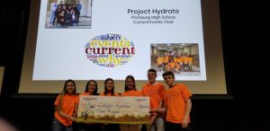 6 teens stand in front of a slideshow while holding a giant check