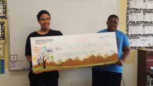 2 kids stand behind a giant check