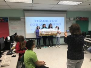 4 kids stand holding a giant check while a woman takes a picture of them