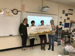 4 teens stand behind a giant check