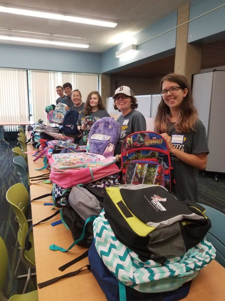 Students stuffing backpacks with school supplies for area foster children