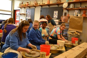 Four students working on pottery wheels