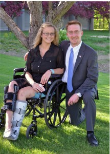 Alexis Maillet sitting in her wheelchair and Christopher Brown kneeling beside her under a tree