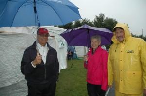 President Daniel Asquino, Chris Kisiel and Ed Terceiro in rain jackets and under umbrellas