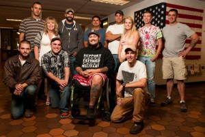 Group of staff members and student Veterans in front of the flag