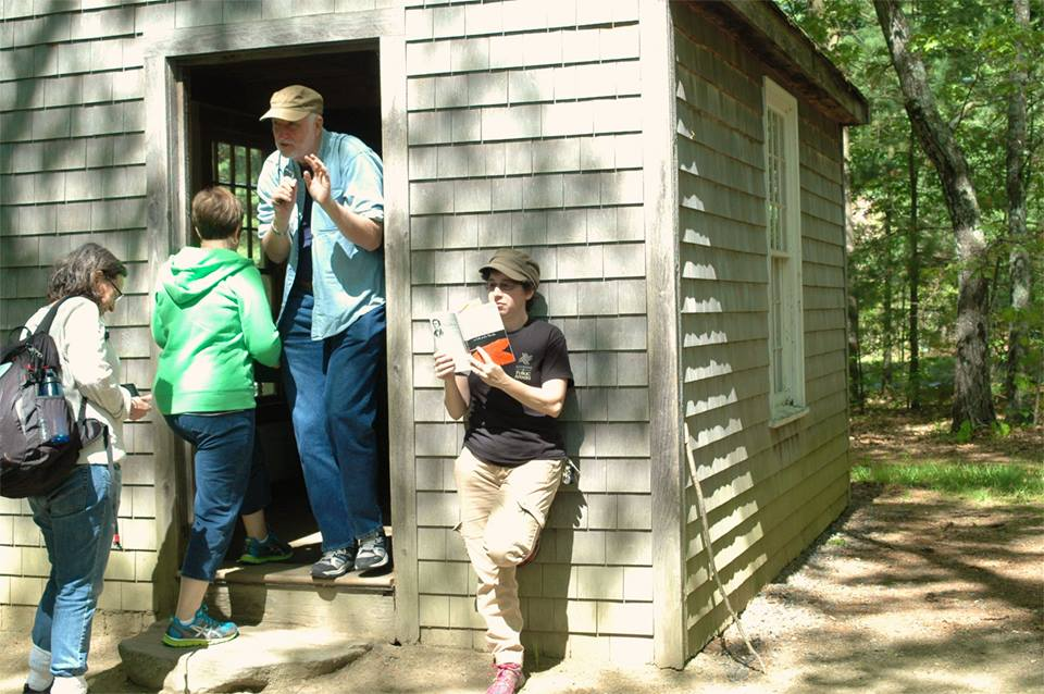Three faculty walking into Walden's cabin while a student reads the book outside next to the door