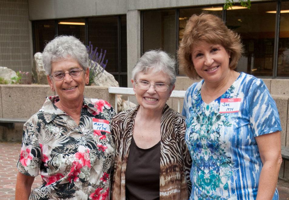 Three nursing alumni posing for a photo outside the Gardner campus