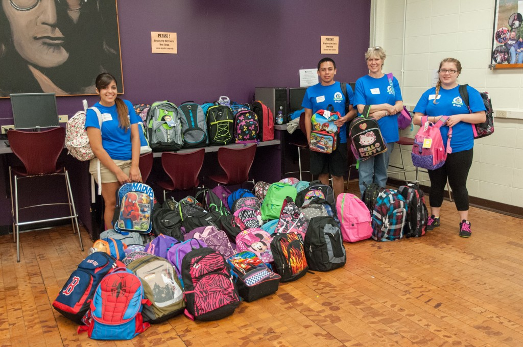 Group of student volunteers with the pile of backpacks that they put together