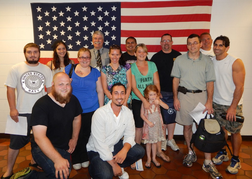 Group of veteran students with Veterans Director, Bob Mayer, in front of the American flag