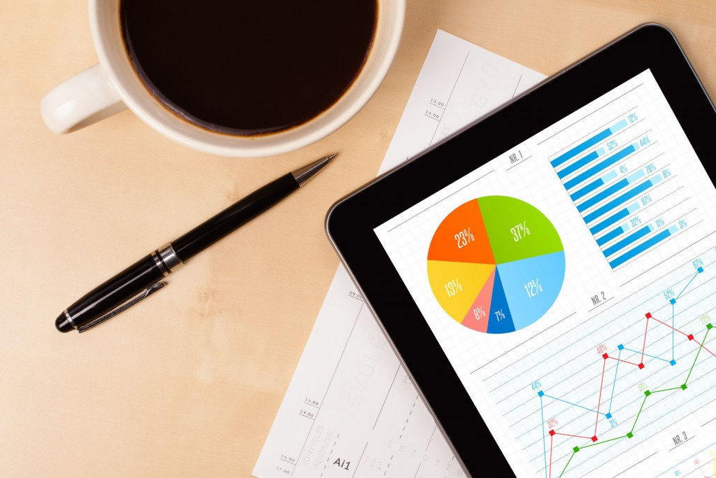 Business items on a desk [coffee, pen, report, ipad with charts on the screen]