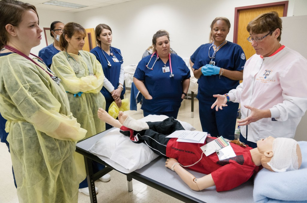 Group of nursing students surrounding a simulated injured patient