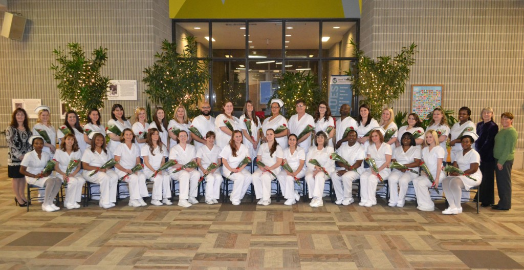 Group of nursing graduates in their nursing attire with flowers in the Commons