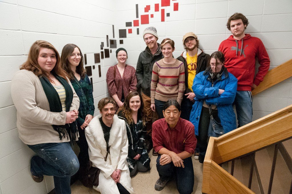 Group of art students standing in the stairwell in front of a red and black abstract installation