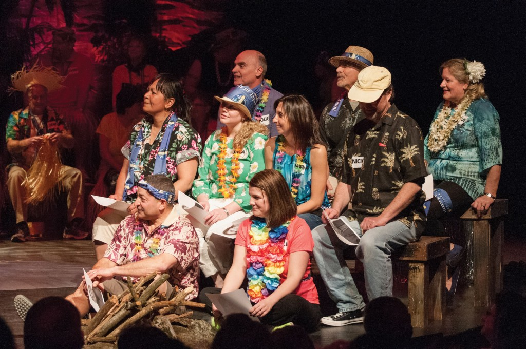 Group of Survivor participants on stage in Hawaiian shirts and leis