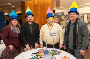 """The Trivial Pursuits"" team, four members with Trivial Pursuit pieces on their hats"