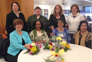 Group of women mentors sitting at a table with flowers on it